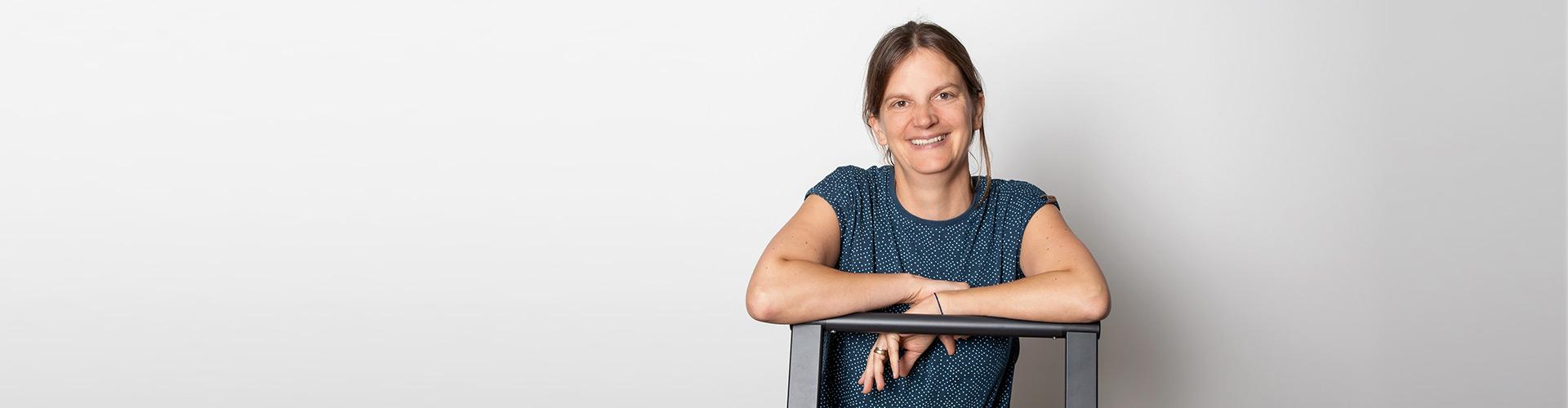 An einen Stuhl gelehnt erläutert die Psychologin Anna Möller-Wolf ihre Biografie.