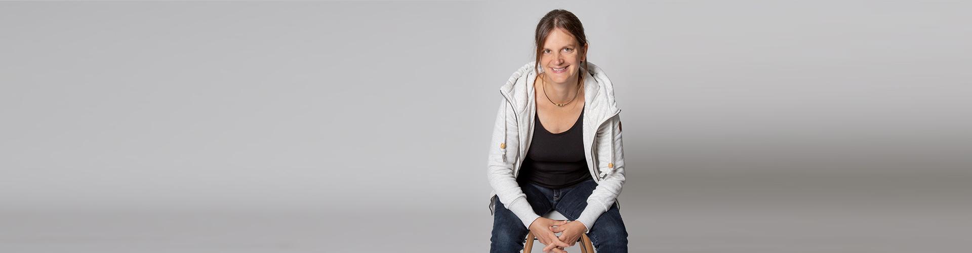 Anna Möller Wolf, Kinder- und Jugendlichenpsychotherapeutin sitzt auf einem Hocker und lächelt.